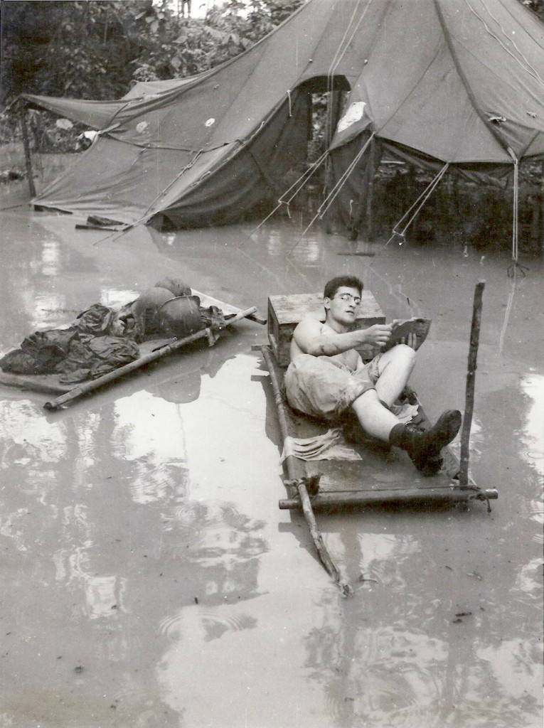 "Books provided a respite from the war and the miserable conditions men lived under.  Here, an American reads an Armed Services Edition in what remained of his ""camp"" in New Guinea.  Surrounded by water, he propped a stretcher up on stilts, used a wooden box for a pillow, and appears to genuinely relax while reading his book.  Books were cherished for their ability to transport minds elsewhere, away from the discomforts and horrors of war. Photo Credit: Australian War Memorial"