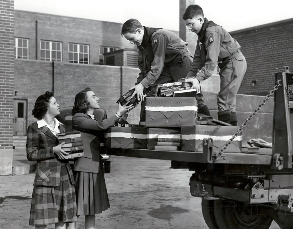 Everyone participated, including children.  Here, boy scouts collect books from women donating armfuls of reading material.